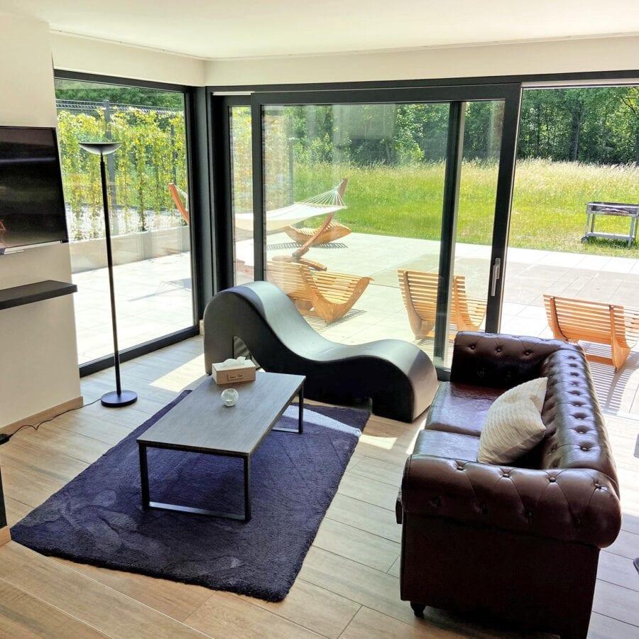 Côté salon et vue sur la terrasse avec piscine au Fermage près de Namur