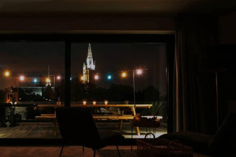 Vue de nuit par la baie vitrée au Studio Rooftop 360 à Ypres
